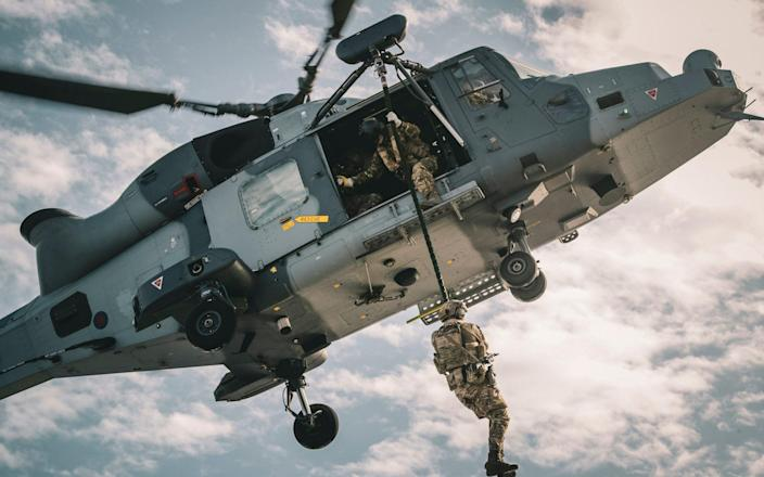 A Royal Marine fast roping from a Wildcat helicopter whilst on exercise in Cyprus, operating from the Amphibious Flag Ship, HMS Albion. - LPhot Barry Swainsbury/Royal Navy