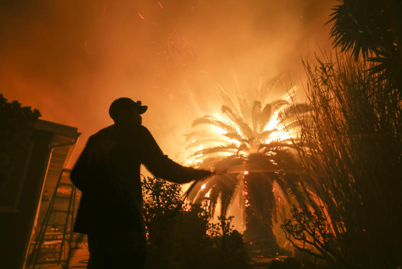 FILE - In this Nov. 9, 2018, file photo, Park Billow, 27, sprays water on the hot spots in his backyard as the Woolsey Fire burns in Malibu, Calif. Los Angeles County has sued Southern California Edison and parent company Edison International to recover more than $100 million in costs and damages from a wind-driven wildfire that may have been sparked by one of the utility's wires. County Supervisor Sheila Kuehl announced the lawsuit Thursday, April 25, 2019. It's the latest suit against SoCal Edison since the Woolsey Fire, which ignited Nov. 8 and charred more than 150 square miles, destroying 1,643 buildings and damaging another 360 structures. (AP Photo/Ringo H.W. Chiu, File)