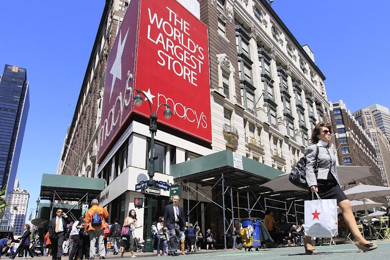 FILE - In this May 10, 2011 file photo, people carrying Macy's shopping bags walk past the Macy's flagship store, in New York. Macy's Inc. is reporting a nearly 16 percent increase in net income for its second quarter Wednesday, Aug. 8, 2012, as the department store chain continues to benefit from its strategy to tailor its merchandise to local markets. Macy's says that its net income rose to $279 million, or 67 cents per share, for the three-month period ended July 28.  (AP Photo/Mary Altaffer, File)