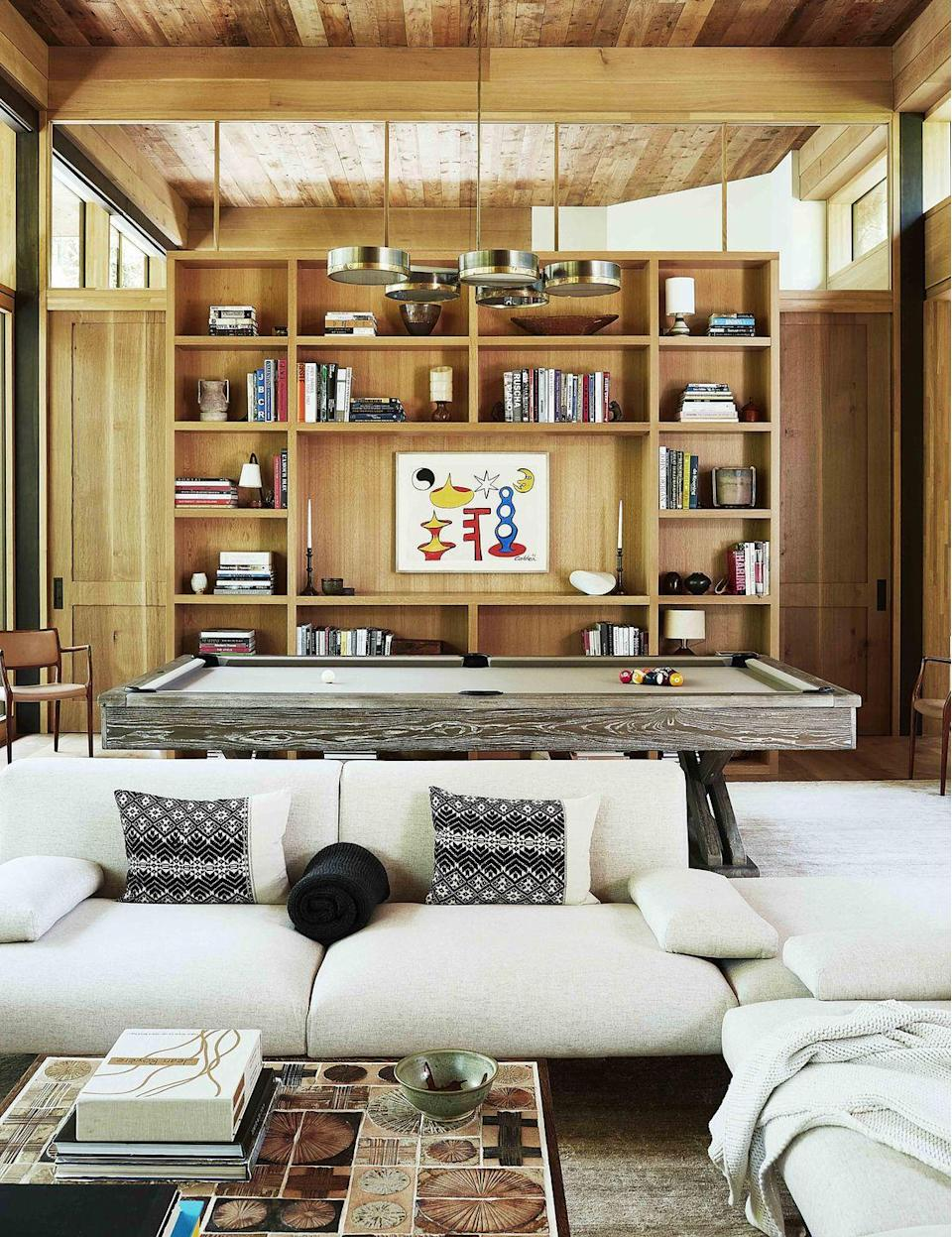 "<p>Well-curated bookshelves exude a sense of class, but there's more to this great room by <a href=""https://www.veranda.com/decorating-ideas/house-tours/a32721436/cliff-fong-north-carolina-lodge/"" rel=""nofollow noopener"" target=""_blank"" data-ylk=""slk:Cliff Fong"" class=""link rapid-noclick-resp"">Cliff Fong</a> than meets the eye. The middle panel actually disappears to reveal a secret walk-in bar behind the oak bookcase, making bar clutter a thing of the past. The artwork is by the late Alexander Calder.</p>"