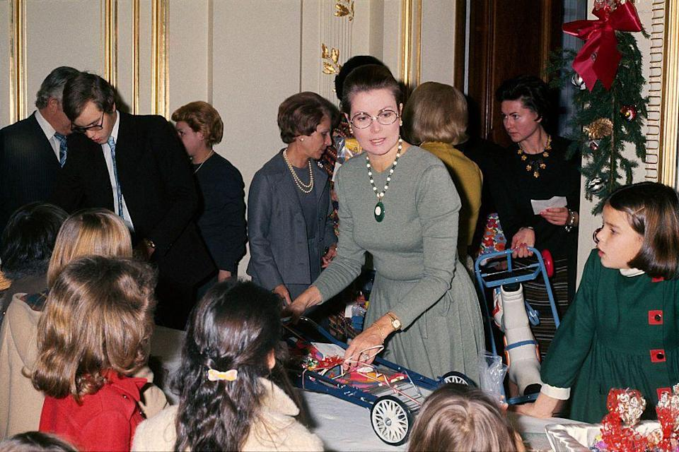 <p>Grace Kelly tends to her royal duties and distributes toys at the palace, along with her children Stephanie and Albert.</p>