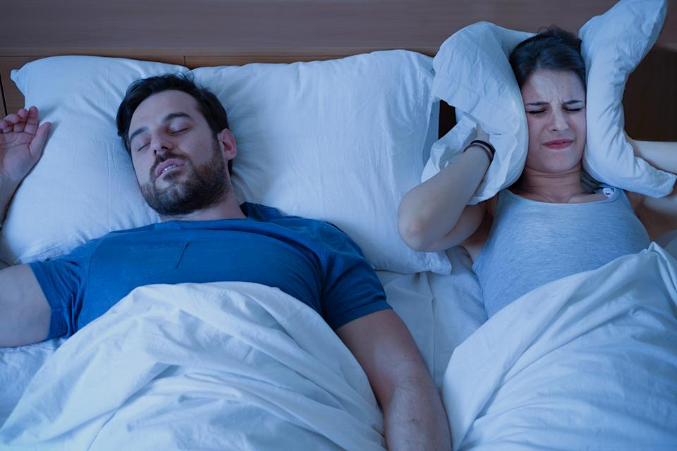 Man snoring in the bed because of night apnoea sleep disorder while woman covers her ears with a pillow