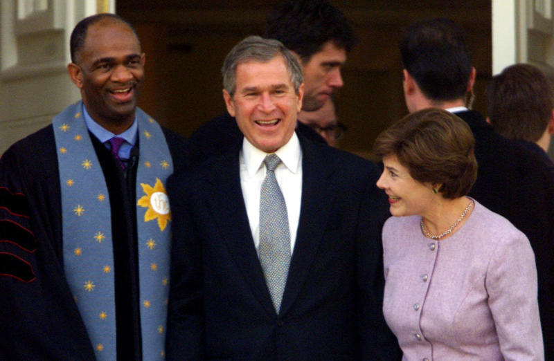 George W. Bush stands with his wife Laura and Rev. Kirbyjon H. Caldwell after services at Tarrytown United Methodist Church in Austin, Texas, on Dec. 14, 2000. Caldwell has long been a spiritual adviser to Bush.