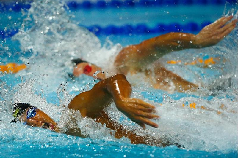 Takeshi Matsuda (L) of Japan and Matt McLean (R) of the US swim in the men's 4 x 200m freestyle relay final at the Gold Coast Aquatic Centre on August 22, 2014 (AFP Photo/PATRICK HAMILTON)