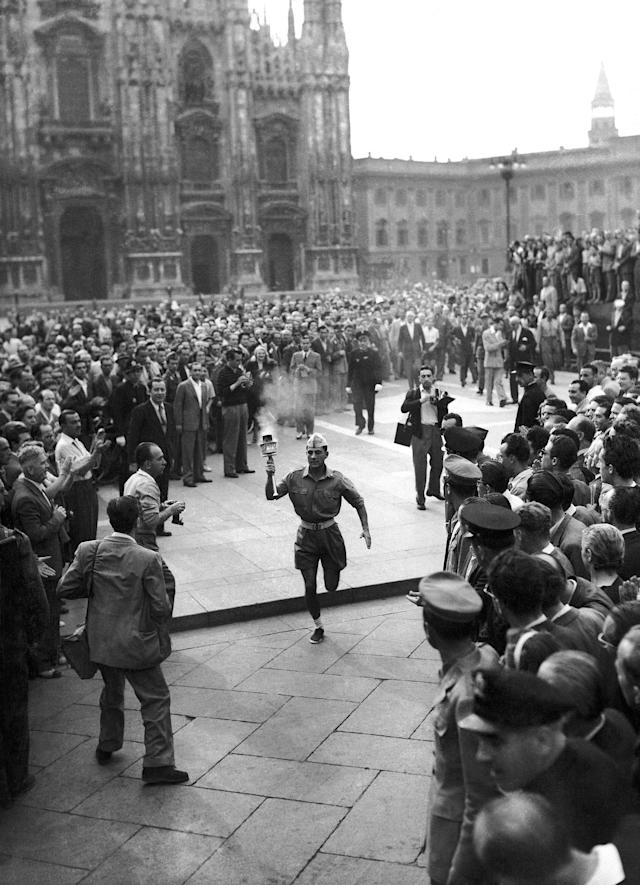The Olympic torch from Olympia, Greece, passed through Milan, Italy on July 23, 1948, on the way to London, United Kingdom, for the opening of the XIV Olympiad. In this image, a lieutenant of the Italian army, torch in hand, is crossing Milan's famous Piazza Del Duomo. The cathedral is seen in the background. (AP Photo)