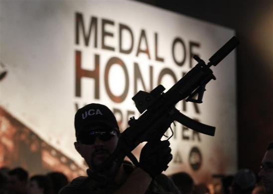 "A man with a toy gun poses in front of an exhibition stand of ""Medal of Honor"" during the Gamescom 2012 fair in Cologne August 16, 2012."