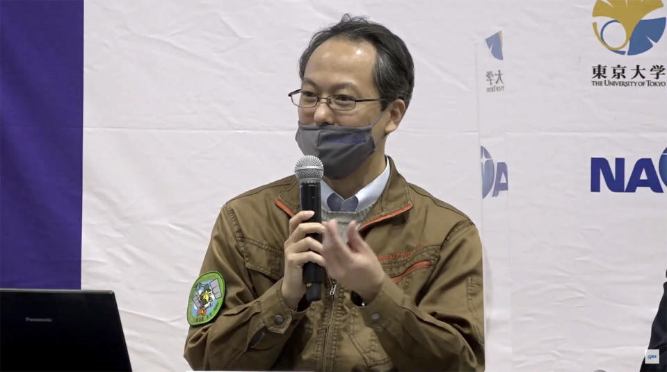 In this image made from youtube video provided by JAXA, its project manager Yuichi Tsuda speaks during a press conference in Sagamihara, near Tokyo, Friday, Dec. 4, 2020. The Japanese space agency said Friday they are all set for its spacecraft′s final approach to Earth this weekend to deliver a capsule containing valuable samples of a distant asteroid that could provide clues to the origin of the solar system. (JAXA via AP)
