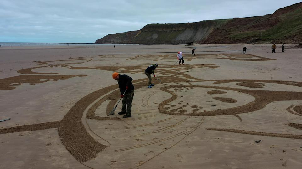 The sand drawing being created on Cayton Bay in Scarborough (Surfers Against Sewage/PA)