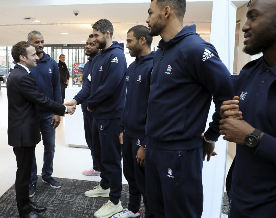 French President Emmanuel Macron, left, shakes hands with national team players as he arrives to inaugurate a new handball stadium in Creteil, on the outskirts of Paris, Wednesday, Jan. 9, 2019. About 200 protesters, including unionists and yellow vests, gathered Wednesday in Creteil, a Paris suburb, as Macron was doing a visit in a facility dedicated to handball. Some scuffles broke out with police forces that used tear gas to keep the crowd at a distance from the French leader. (Ludovic Marin, Pool via AP)