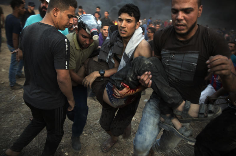 Palestinian protesters evacuate a wounded man shot by Israeli troops during a protest at the Gaza Strip's border with Israel, Friday, Oct. 12, 2018. (AP Photo/Khalil Hamra)