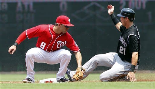 Colorado Rockies' Tyler Colvin (21) safely steals second as Washington Nationals second baseman Danny Espinosa (8) cannot make the tag in time during the second inning of a baseball game, Sunday, July 8, 2012, in Washington. (AP Photo/Alex Brandon)
