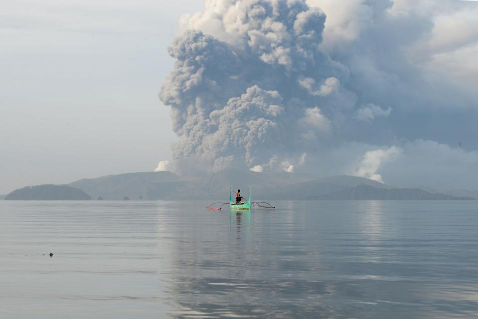 FILE PHOTO: A youth living at the foot of Taal volcano rides an outrigger canoe while the volcano spews ash as seen from Tanauan town in Batangas province, south of Manila, on January 13, 2020. (Photo by TED ALJIBE/AFP via Getty Images)