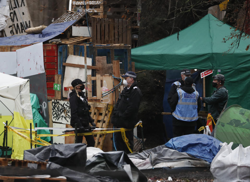 Police officers work to clear an HS2 protest camp outside Euston station in London, Thursday, Jan. 28, 2021. Some protesters against a high-speed rail link between London and northern England were evicted from a park in the capital city early Wednesday after they dug tunnels and set up a makeshift camp. (AP Photo/Alastair Grant)