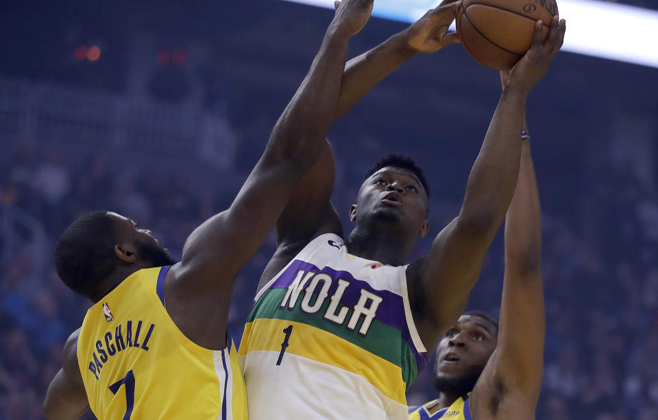 New Orleans Pelicans' Zion Williamson, center, shoots between Golden State Warriors' Eric Paschall (7) and Kevon Looney, right, in the first half of an NBA basketball game Sunday, Feb. 23, 2020, in San Francisco. (AP Photo/Ben Margot)