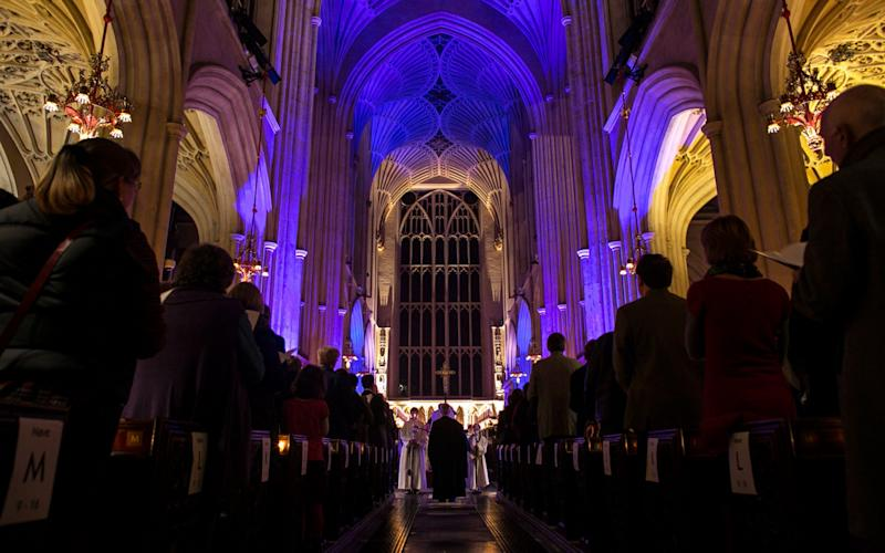 The congregation watch as choristers take part in Bath Abbey's candlelit Advent Procession on December 1, 2013 in Bath, England - Credit: Matt Cardy/Getty Images Europe