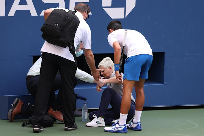 Novak Djokovic of Serbia tends to a lineswoman after inadvertently striking her with a ball hit in frustration during his match against Pablo Carreno Busta of Spain at the US Open on Sunday. (Al Bello/Getty Images)