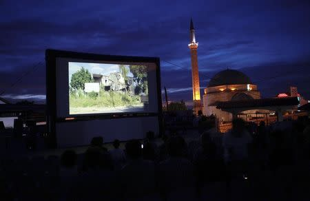 Kosovars and foreign visitors take their seats on a raised platform to watch a documentary film during Dokufest in Prizren