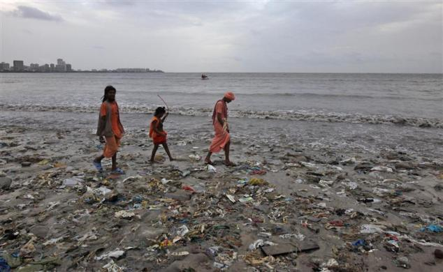 Ram Singh (L) and his relatives, dressed in traditional Hindu saffron-colored clothes walk on a garbage-strewn beach against the backdrop of monsoon clouds on World Environment Day in Mumbai, June 5, 2012. According to the United Nations Environment Programme (UNEP) website, World Environment Day is celebrated annually on June 5 to raise global awareness and motivate action for environmental protection.