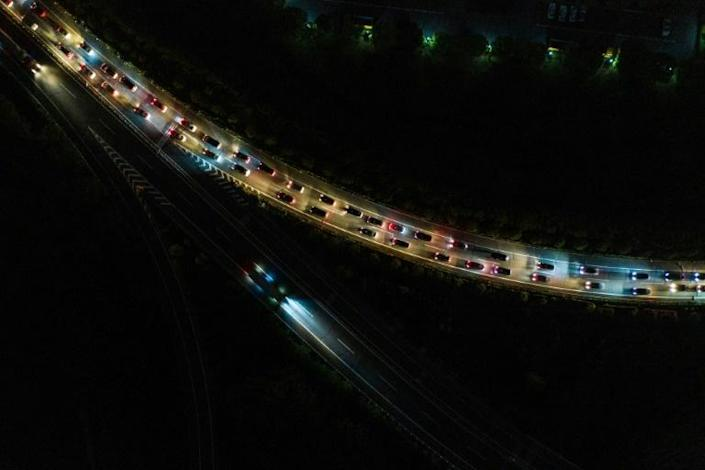 Cars queued at highway toll stations in Wuhan on Wednesday night as they prepared to leave the city (AFP Photo/STR)