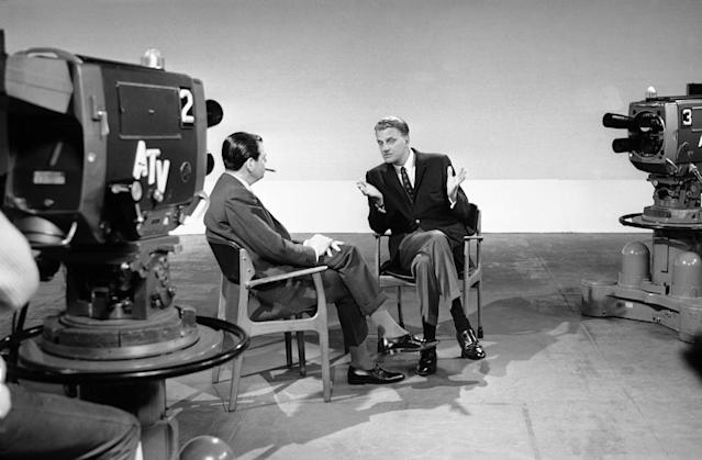 "<p>Billy Graham, right, talks to Kenneth Harris at A.T.V. studios at Elstree, near London, May 26, 1966, while recording an interview for the program ""About Religion."" (Photo: AP) </p>"