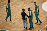 Brooklyn Nets guard Kyrie Irving, center, greets former teammate Boston Celtics guard Jaylen Brown as Celtics' Daniel Theis, right, looks on before an NBA preseason basketball game, Friday, Dec. 18, 2020, in Boston. (AP Photo/Mary Schwalm)