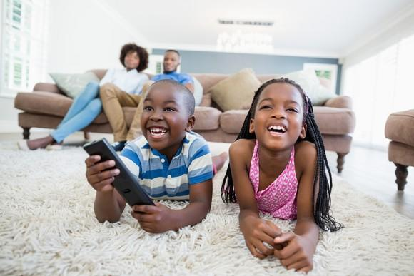 Smiling kids lying on a rug and watching television with their parents on the couch in the background.