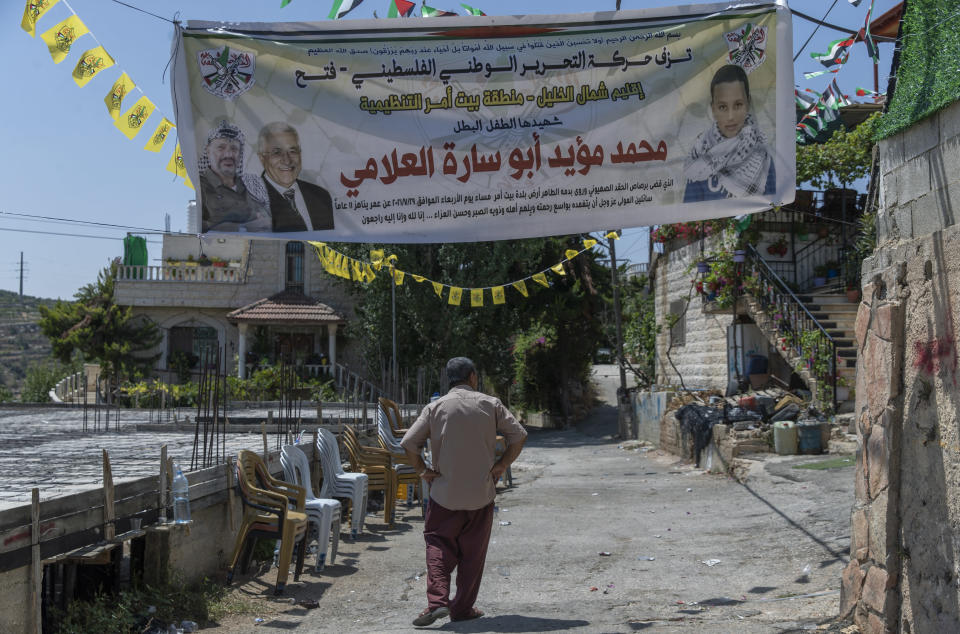 """A Palestinian man passes under a banner with picture and name of slain Mohammed al-Alami, 12 and reads """"Palestinian National Liberation movement, Fatah, offers her hero martyr child,"""" infant of the family house, in the West Bank village of Beit Ummar, near Hebron, Wednesday, Aug. 4, 2021. (AP Photo/Nasser Nasser)"""