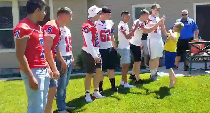 Photo showing Christian, 9, excitably high-fiving football players that came to his birthday in Meridan, Idaho.