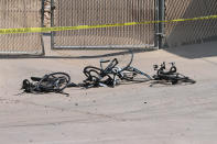 This Saturday, June 19, 2021, photo courtesy of The White Mountain Independent shows the scene of an accident with broken bicycles in Show Low, Ariz. A driver in a pickup truck plowed into bicyclists competing in a community road race in Arizona on Saturday, critically injuring several riders before police chased down the driver and shot him outside a nearby hardware store, police said. (Jim Headley/The White Mountain Independent via AP)