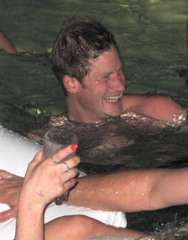 "EXCLUSIVE: **PREMIUM RATES APPLY** Prince Harry parties at XS Nightclubs ""Sunday Night Swim Party"". Prince Harry was at a pool side daybed with friends, ladies and heavy security. Harry arrived in a blue button-up shirt, but soon took it off and jumped in the pool with only his blue jeans. He had gun being on the Swan floatie and tipping his boys off it. He was also joined by random ladies on the swan for a while.