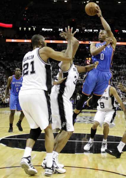 Oklahoma City Thunder point guard Russell Westbrook (0) looks to pass against San Antonio Spurs center Tim Duncan (21) and power forward Boris Diaw during the first half of Game 5 in the NBA basketball Western Conference finals, Monday, June 4, 2012, in San Antonio. (AP Photo/Eric Gay)