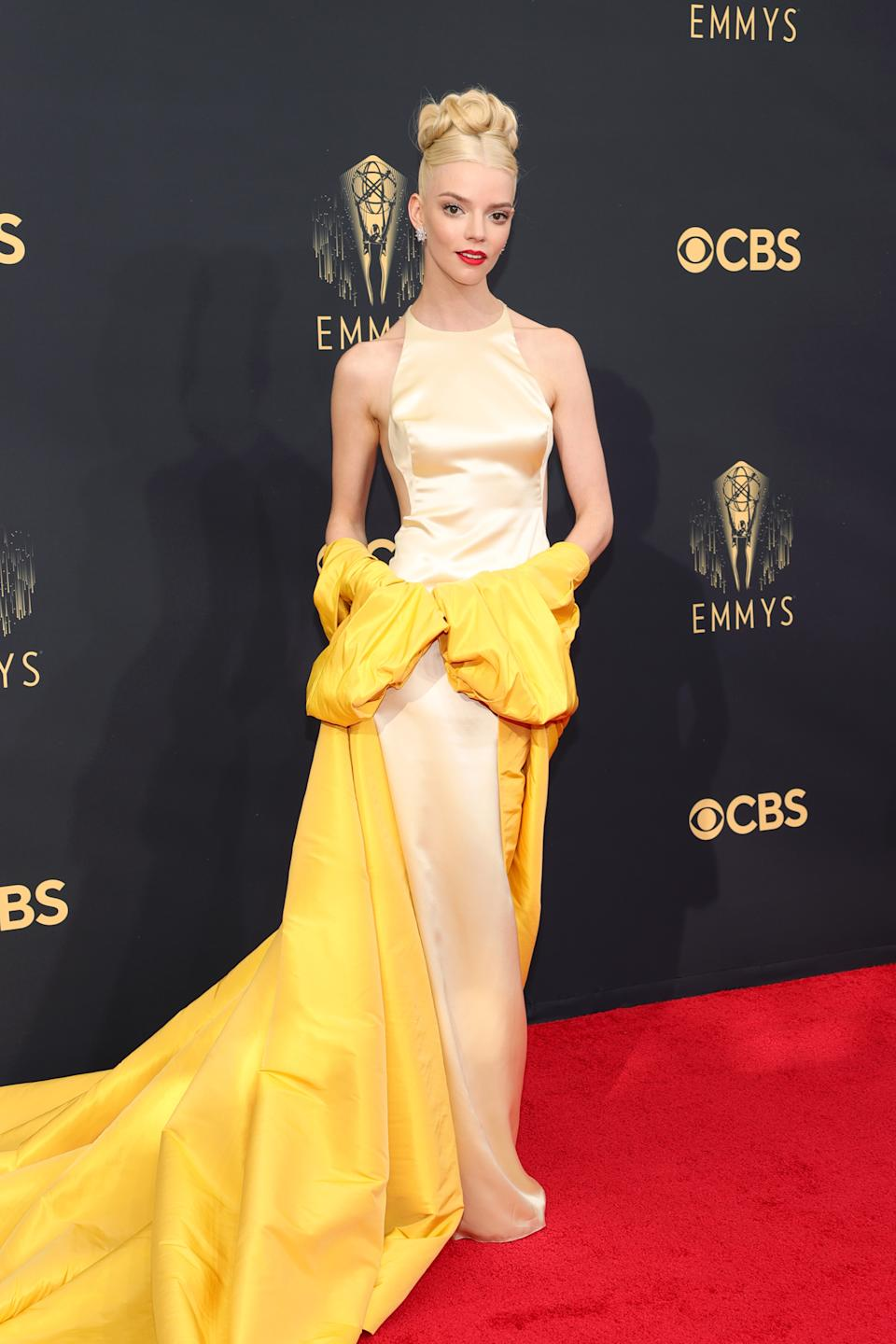 Anya Taylor-Joy wears a cream and yellow dress at the 73rd Primetime Emmy Awards at L.A. LIVE on September 19, 2021 in Los Angeles, California