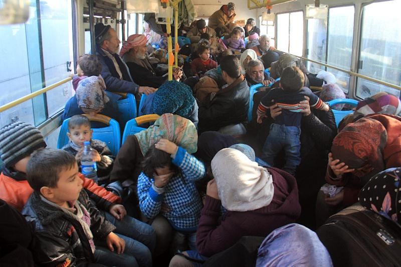 Residents from the mostly Shiite Syrian villages of Kafraya and Fuaa, which are besieged by opposition fighters, wait in a bus to get a green light from the rebels to cross into a government controlled area in the province of Aleppo (AFP Photo/Omar haj kadour)