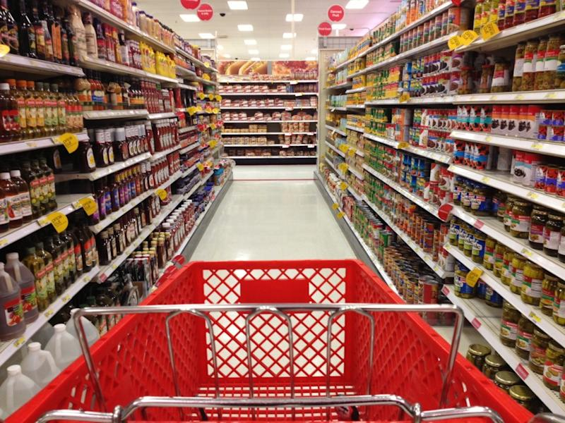 A red shopping cart in the middle of a food aisle in Target.