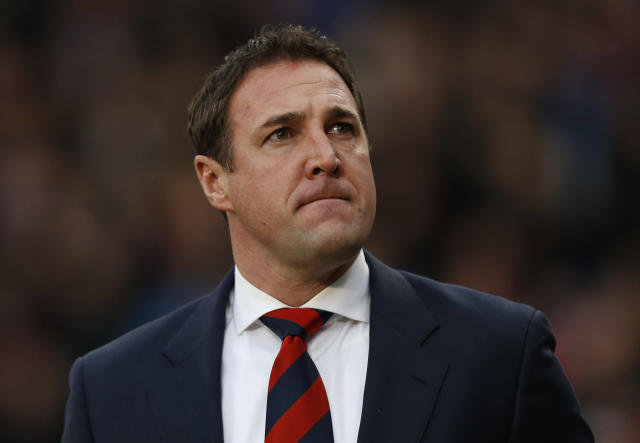 Cardiff City's manager Malky Mackay arrives at the dugout before the start of their English Premier League soccer match against Crystal Palace at Selhurst Park, London, Saturday, Dec. 7, 2013. (AP Photo/Sang Tan)