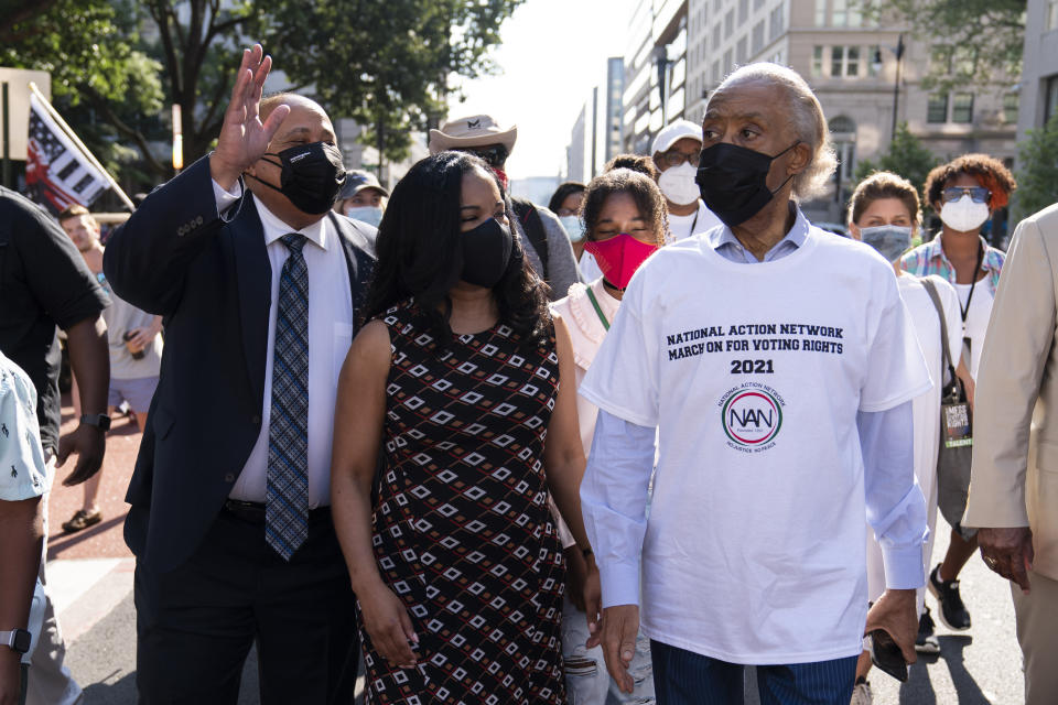 The Rev. Al Sharpton, right, with Martin Luther King, III, left, walk during a march for voting rights, marking the 58th anniversary of the March on Washington, Saturday, Aug. 28, 2021, in Washington. Hundreds of thousands of voting rights advocates rallied across the country Saturday to call for sweeping protections against a further erosion of the Voting Rights Act of 1965. (AP Photo/Jose Luis Magana)