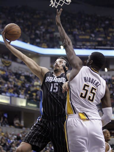 Orlando Magic forward Hedo Turkoglu, left, shoots under Indiana Pacers center Roy Hibbert in the first half of an NBA first-round playoff basketball game in Indianapolis, Saturday, April 28, 2012.  (AP Photo/Michael Conroy)