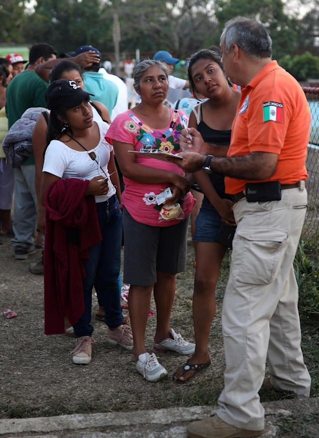 <p>A Mexican immigration worker speaks to Central American migrant women as he carries out out paperwork for migrants wishing to apply for refugee status in Mexico, as he canvases people participating in the Migrant Stations of the Cross caravan that has set up camp at a sports center in Matias Romero, Oaxaca state, Mexico, late Monday, April 2, 2018. (Photo: Felix Marquez/AP) </p>