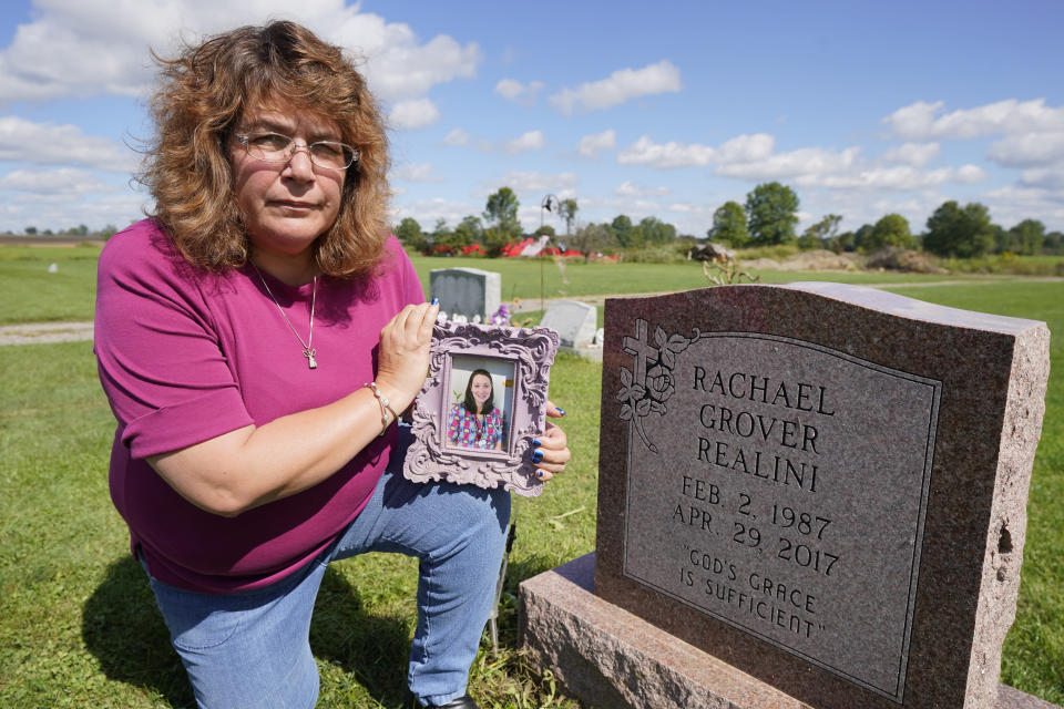 Sharon Grover holds a photograph of her daughter, Rachael, over the gravesite at Fairview Cemetery, Tuesday, Sept. 28, 2021, in Mesopotamia, Ohio. Grover believes her daughter started using prescription painkillers around 2013 but missed any signs of her addiction as her daughter, the oldest of five children, remained distanced. (AP Photo/Tony Dejak)