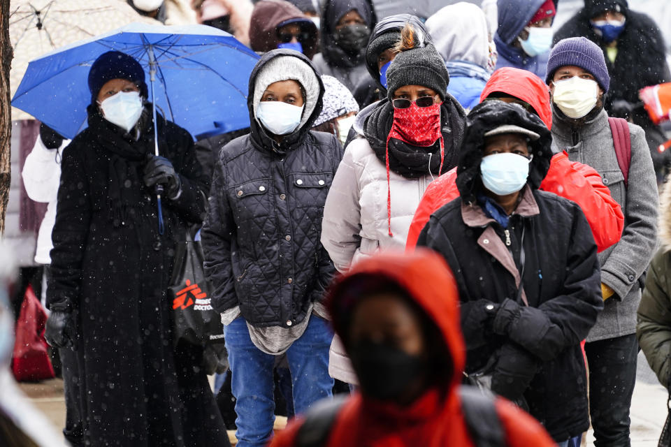 FILE - In this Feb. 19, 2021, file photo, people wait in line at a 24-hour, walk-up COVID-19 vaccination clinic hosted by the Black Doctors COVID-19 Consortium at Temple University's Liacouras Center in Philadelphia. More Black Americans say they are open to taking the coronavirus vaccine amid campaigns to overcome a shared historical distrust of science and government. (AP Photo/Matt Rourke, File)