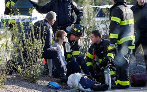 A woman is aided by first responders after sustaining injury on a bike path in lower Manhattan in New York - Credit: REUTERS/Brendan McDermid