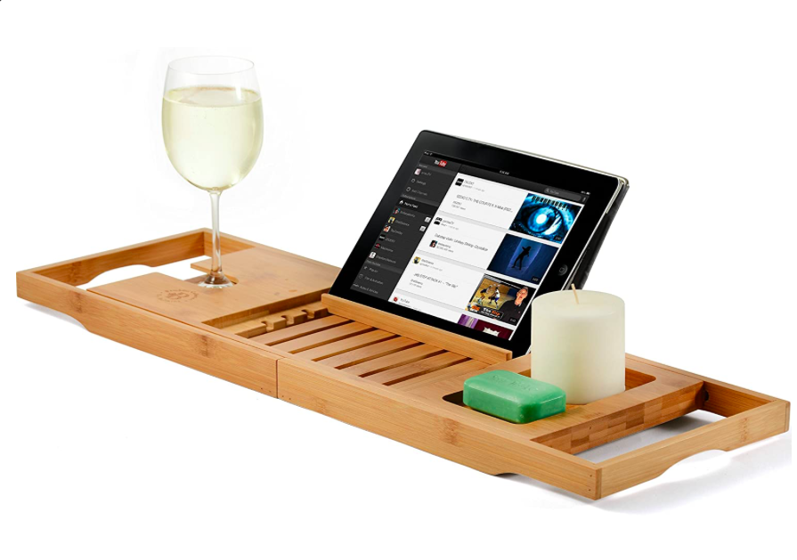 """<h2>Premium Bamboo Bathtub Caddy</h2><br>While we may not all have a bathroom that could actually be called """"premium"""", we can get one step closer to an aspirational <em>salle de bains</em> with the help of this spa-like bathtub caddy. While contraptions like these abound on Amazon, hundred of reviews attest to the thoughtful, no-slip design and ample storage of this particular iteration. """"This is a great bath caddy that has everything I could possibly need to make my bath time perfect,"""" wrote reviewer Joan S. """"The wine holder, iPad/book holder, phone holder, soap holder... they thought of everything. And I LOVE the bamboo. It's so solid and sturdy, but it looks so beautiful. The rubber grips are great at keeping it in place, too.""""<br><br><strong>4.6 out of 5 stars and 1,466 reviews</strong><br><br><strong>Bambüsi</strong> Premium Bamboo Bathtub Tray Caddy, $, available at <a href=""""https://amzn.to/3lLqsvH"""" rel=""""nofollow noopener"""" target=""""_blank"""" data-ylk=""""slk:Amazon"""" class=""""link rapid-noclick-resp"""">Amazon</a>"""