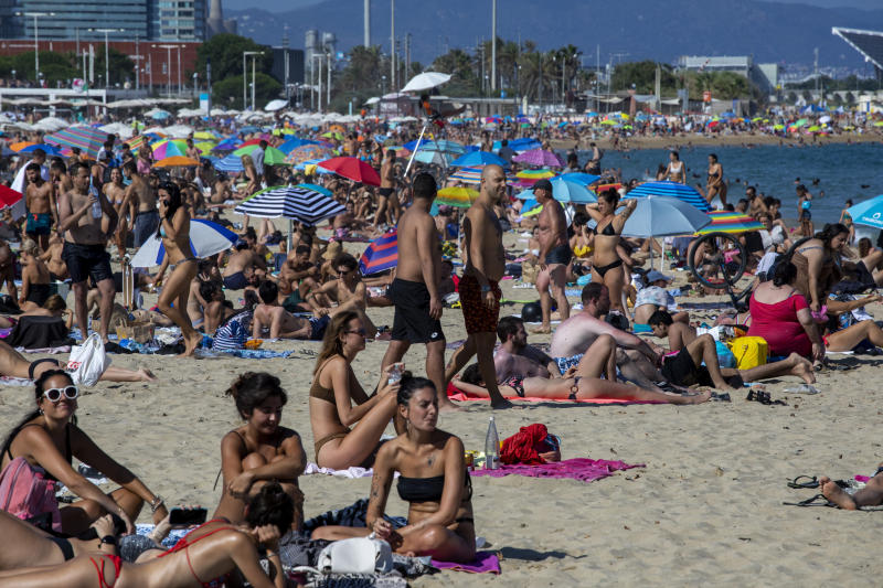 People enjoy the beach in Barcelona, Spain, Saturday, July 18, 2020. Police in Barcelona are closing access to a large area of the city's beaches due to the excess of sunbathers who decided to ignore the urgings of authorities to stay at home amid a resurgence of the coronavirus. (AP Photo/Emilio Morenatti)