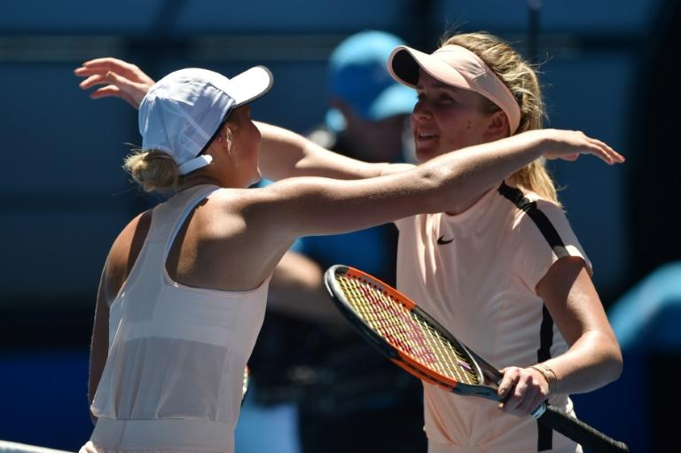 Ukraine's Marta Kostyuk (L) congratulates compatriot Elina Svitolina after their Australian Open third round match, in Melbourne, on January 19, 2018