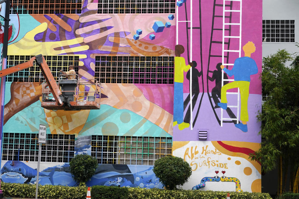 Mural artist Kyle Holbrook paints a mural, Wednesday, July 14, 2021, in Miami, in the memory of the victims of the Champlain Towers South building in Surfside, Fla. which partially collapsed nearly three weeks ago. (AP Photo/Lynne Sladky)