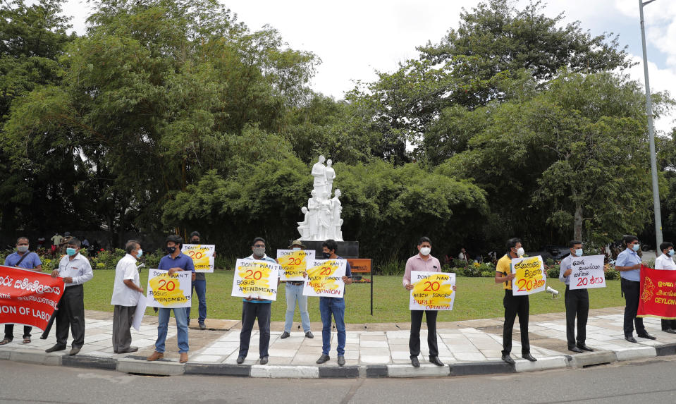 Sri Lankan trade union and civil society activists hold placards outside the parliament as they protest against a proposed constitution amendment that would consolidate power in the president's hands in Colombo, Sri Lanka, Wednesday, Oct. 21, 2020. (AP Photo/Eranga Jayawardena)