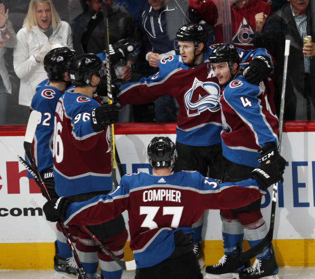 Colorado Avalanche center Nathan MacKinnon, back center, is congratulated after his power-play goal by teammates Gabriel Landeskog, back left, and Mikko Rantanen, front left, J.T. compeer, front, and Tyson Barrie in the first period of Game 3 of a first-round NHL hockey playoff series against the Calgary Flames, Monday, April 15, 2019, in Denver. (AP Photo/David Zalubowski)