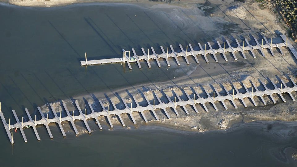 FILE - The shallow water is seen from above at a boat dock on May 13, 2021, at Antelope Island, Utah. The water levels at the Great Salt Lake have hit a historic low, a grim milestone for the largest natural lake west of the Mississippi River that comes as a megadrought grips the region. (AP Photo/Rick Bowmer, File)