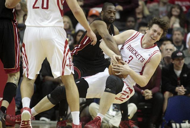 Houston Rockets center Omer Asik (3) struggles with Miami Heat guard Dwyane Wade for a jump ball during the first half of an NBA basketball game, Tuesday, March, 4, 2014, in Houston. (AP Photo/Patric Schneider)