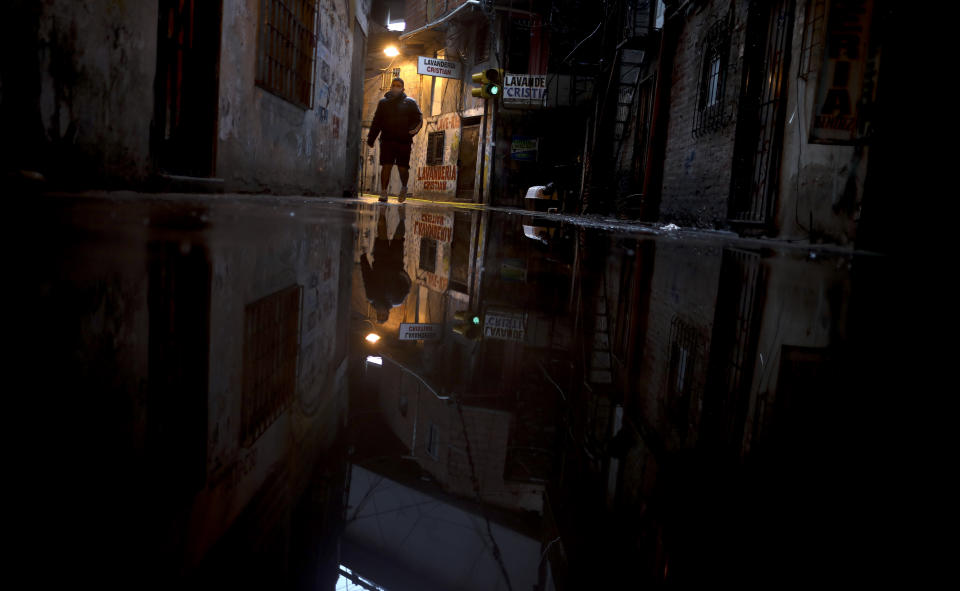 A man walks at 31 slum during a government-ordered lockdown to curb the spread of the new coronavirus in Buenos Aires, Argentina, Tuesday, April 28, 2020. (AP Photo/Natacha Pisarenko)